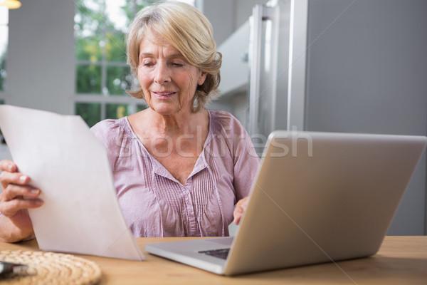 Sorridente mulher madura usando laptop leitura arquivo computador Foto stock © wavebreak_media