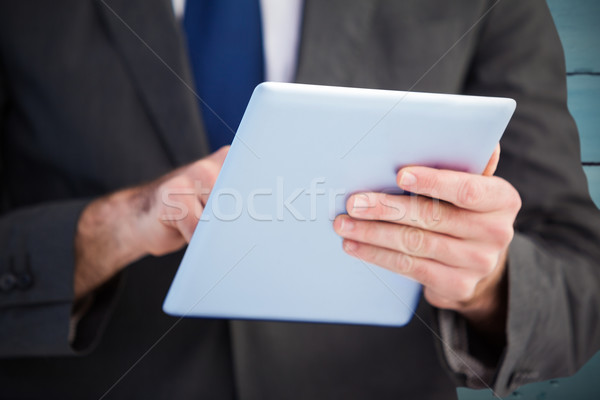 Composite image of businessman scrolling on his digital tablet Stock photo © wavebreak_media