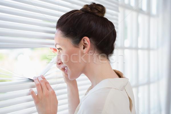 Woman peeking through the blinds Stock photo © wavebreak_media