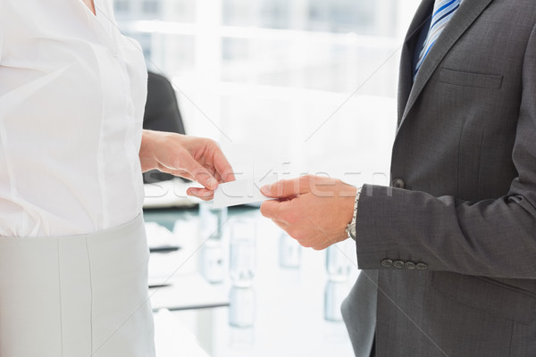 Businessman handing businesswoman a card Stock photo © wavebreak_media