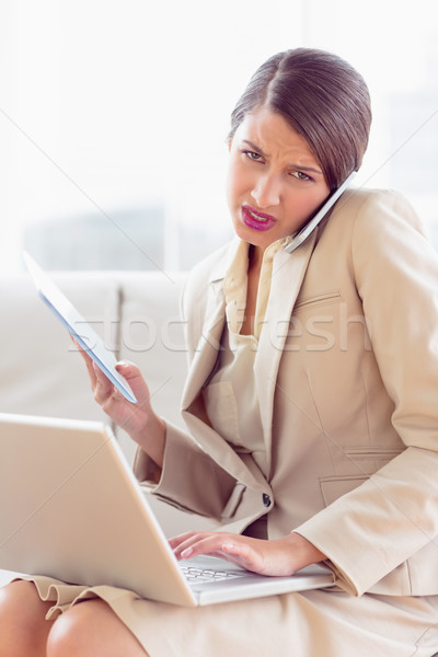 Busy and stressed businesswoman sitting on sofa multi tasking Stock photo © wavebreak_media