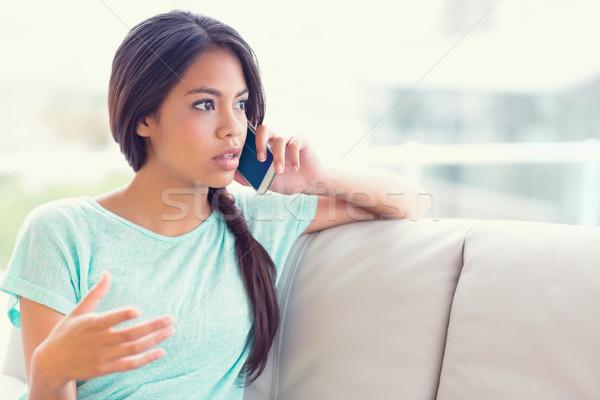 Serious girl sitting on sofa making a phone call Stock photo © wavebreak_media