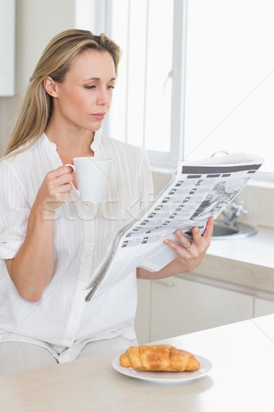 Serious woman holding mug and newspaper at breakfast Stock photo © wavebreak_media