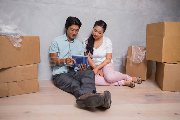 Happy couple sitting on floor using tablet surrounded by boxes Stock photo © wavebreak_media