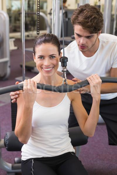 S'adapter brunette poids machine bras entraîneur Photo stock © wavebreak_media