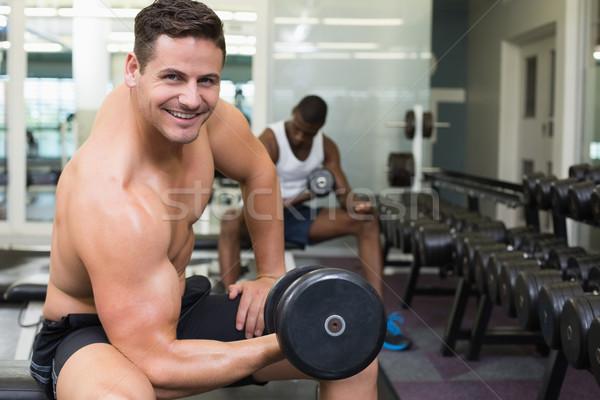 Handsome bodybuilder lifting heavy dumbbell smiling at camera Stock photo © wavebreak_media