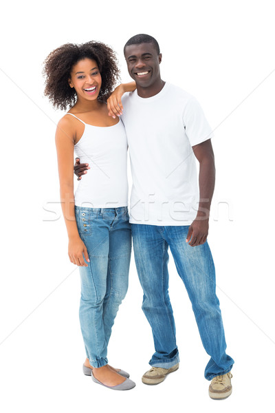 Casual couple in jeans and white tops smiling at camera Stock photo © wavebreak_media