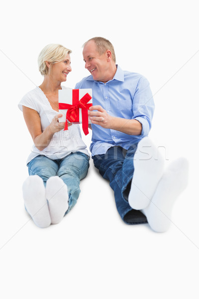 Happy mature couple holding a gift Stock photo © wavebreak_media