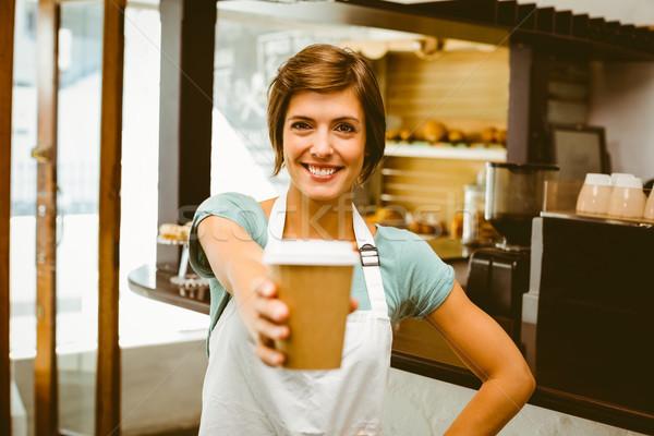 Pretty barista smiling at camera holding disposable cup Stock photo © wavebreak_media