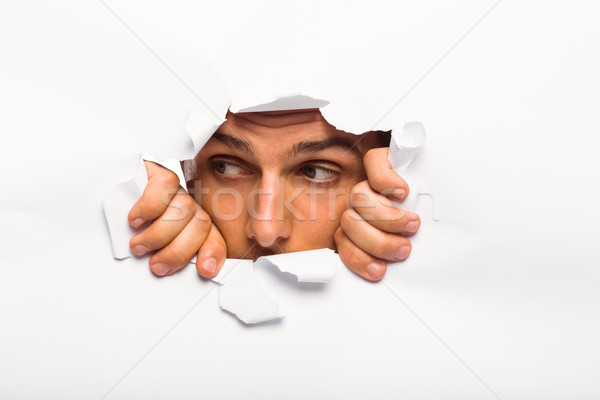 Young man looking through paper rip Stock photo © wavebreak_media