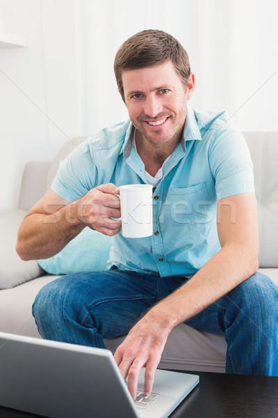 笑みを浮かべて 男 マグ ラップトップを使用して 座って ソファ ストックフォト © wavebreak_media