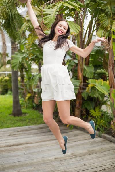 Bastante morena saltando para cima sorridente fora Foto stock © wavebreak_media