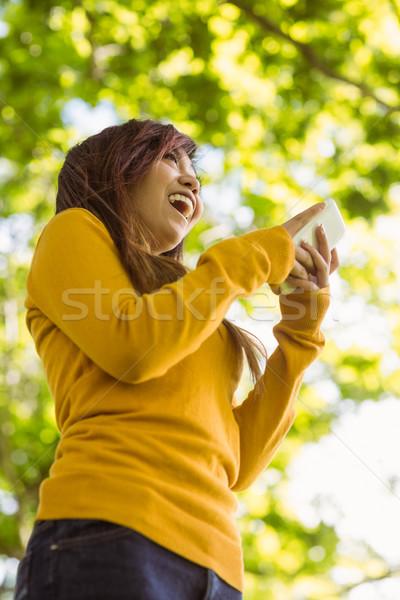 Gyönyörű fiatal nő sms üzenetküldés park alulról fotózva kilátás Stock fotó © wavebreak_media
