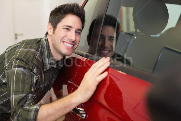 Smiling man hugging a red car Stock photo © wavebreak_media