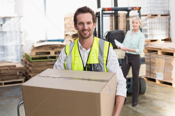 Smiling warehouse worker carrying box Stock photo © wavebreak_media