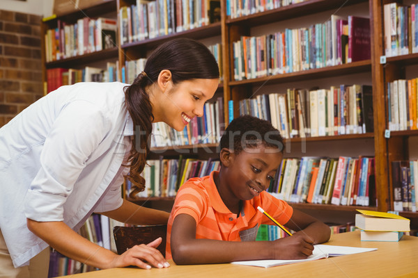Teacher assisting boy with homework in library Stock photo © wavebreak_media
