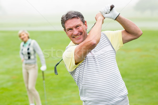 Happy golfer teeing off with partner behind him  Stock photo © wavebreak_media