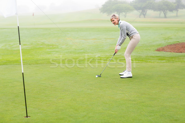 Stock photo: Lady golfer on the putting green