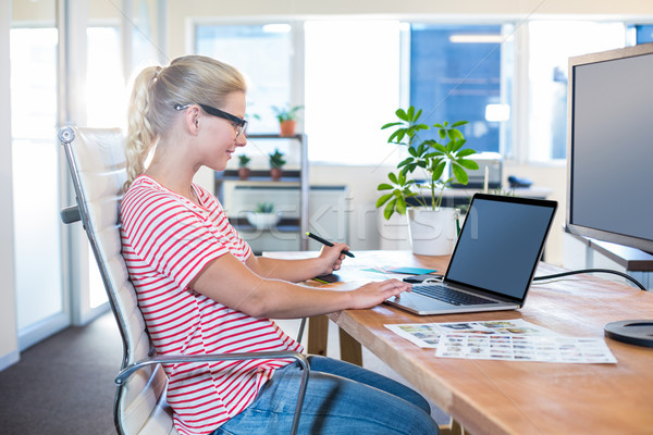 Cheerful casual businesswoman using laptop and digitizer Stock photo © wavebreak_media