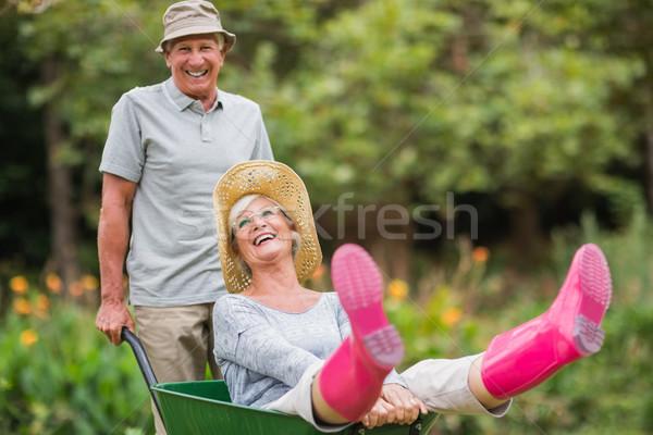 Feliz casal de idosos jogar carrinho de mão mulher Foto stock © wavebreak_media