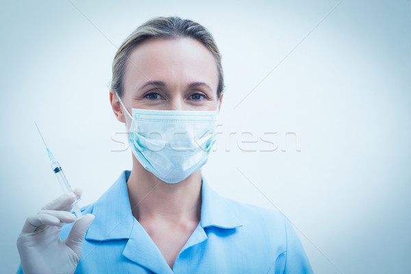 Female dentist in surgical mask holding injection Stock photo © wavebreak_media