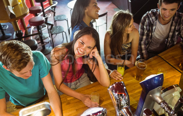 Smiling friends talking and drinking beer and mixed drink Stock photo © wavebreak_media