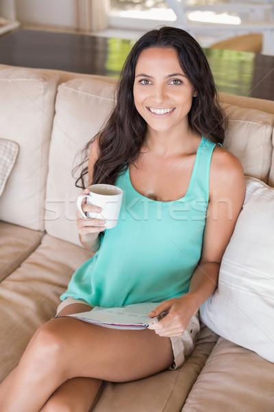 Bella bruna lettura magazine divano home Foto d'archivio © wavebreak_media