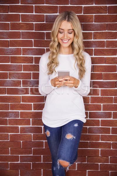 улыбаясь смартфон красный кирпичных Сток-фото © wavebreak_media