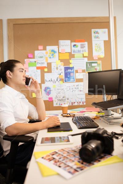 Designer talking on phone while working in creative office Stock photo © wavebreak_media