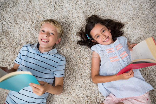 Portrait of siblings lying on rug and reading book in living room Stock photo © wavebreak_media