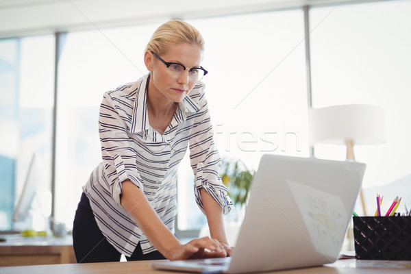 Attentive executive using laptop at desk Stock photo © wavebreak_media