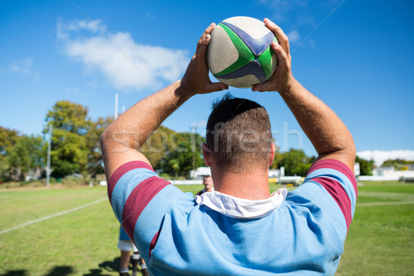 Rear view of rugby player holding ball while standing at grassy field Stock photo © wavebreak_media