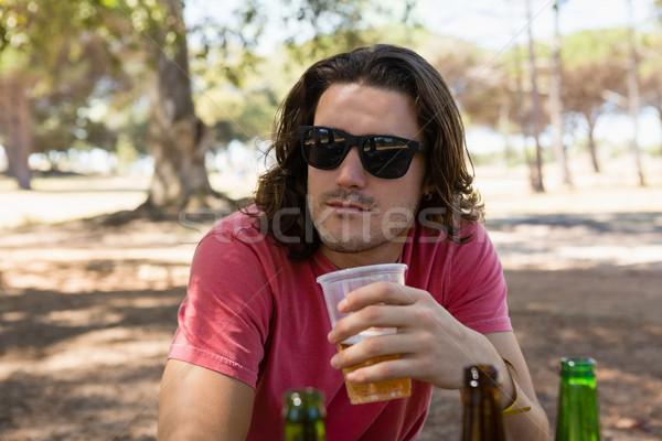 Man in sunglasses having a beer in the park Stock photo © wavebreak_media