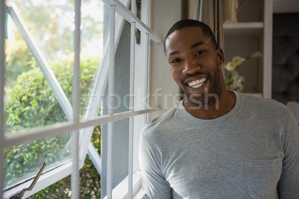 Portrait of smiling man standing by window Stock photo © wavebreak_media