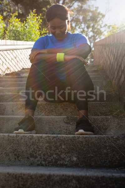 Upset woman sitting on staircase in the boot camp Stock photo © wavebreak_media