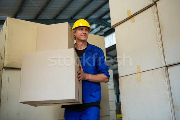 Worker holding a cardboard boxes while walking Stock photo © wavebreak_media