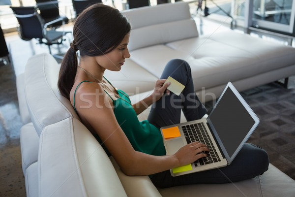 Woman using laptop while relaxing on sofa at office Stock photo © wavebreak_media