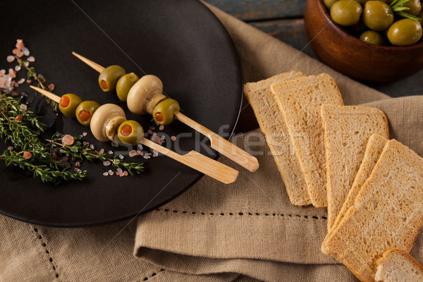Crackers by green olives served in plate Stock photo © wavebreak_media