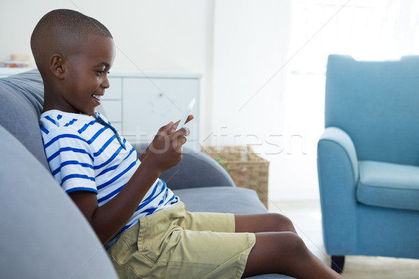 Side view of smiling boy using mobile phone while sitting on sofa at home Stock photo © wavebreak_media