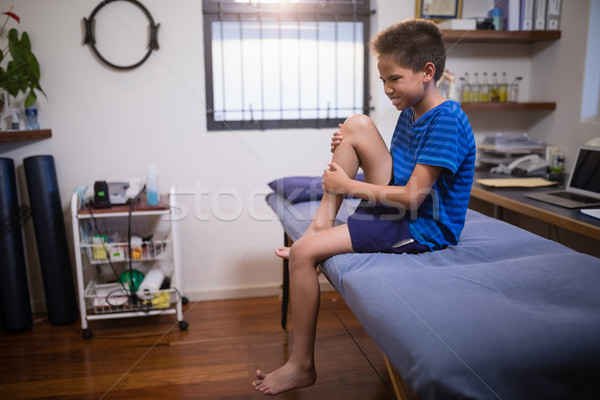 Boy frowning with knee pain while sitting on bed Stock photo © wavebreak_media