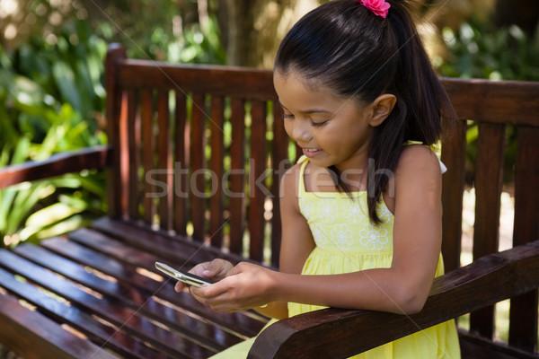 Sorridere ragazza telefono cellulare seduta legno panchina Foto d'archivio © wavebreak_media