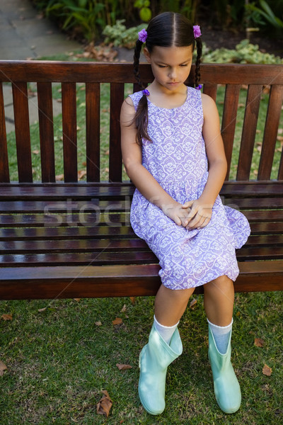 Stock photo: High angle view of upset girl sitting on wooden bench