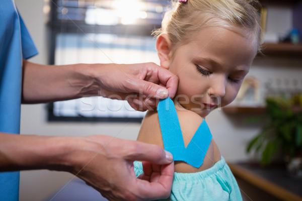 Physiotherapist sticking tape on girl patient Stock photo © wavebreak_media
