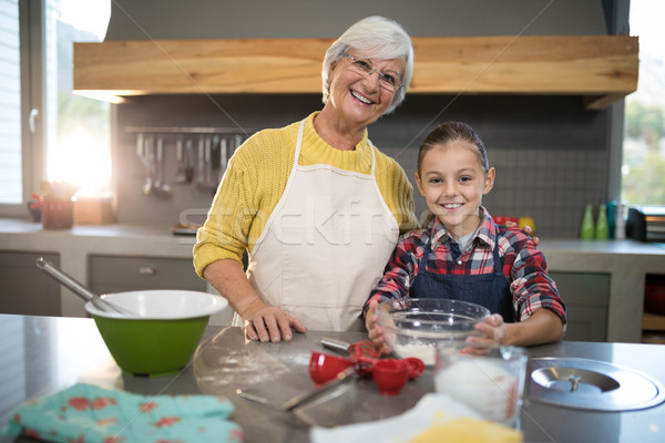 Smiling grandmother and granddaughter holding a bowl of flour in the kitchen Stock photo © wavebreak_media