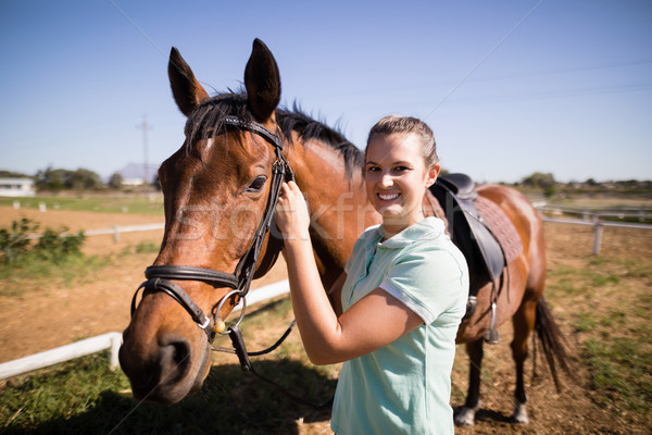 Portrait of female jockey fastening bridle Stock photo © wavebreak_media