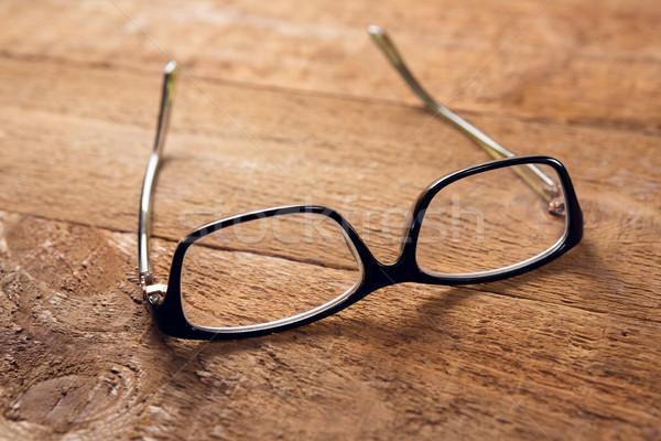 Közelkép szemüveg fa asztal fa keret asztal Stock fotó © wavebreak_media