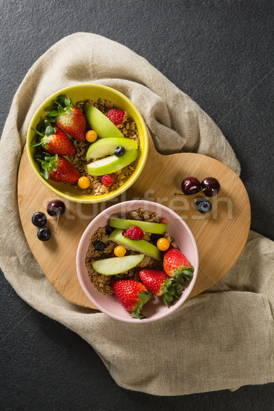 Bowls of breakfast cereals with fruits on chopping board Stock photo © wavebreak_media
