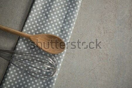 High anlge view of wooden spoon with wire whisk on folded napkin Stock photo © wavebreak_media