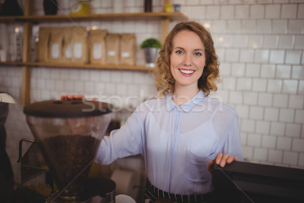 Portrait of smiling young waitress standing by coffee maker Stock photo © wavebreak_media