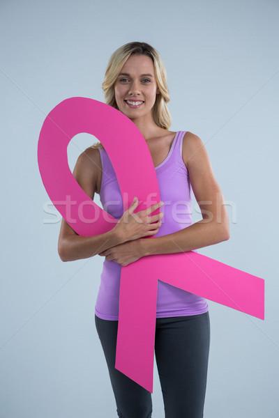Portrait of young female holding cardboard Breast Cancer Awareness ribbon Stock photo © wavebreak_media